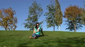 stopa : Woman sits in the park on the green grass barefoot and uses the smartphone Wideo