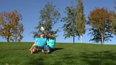 Woman and man sit in the park on the green grass barefoot and take a selfie on a smartphone