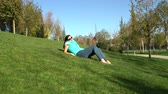 Woman resting in the park lying on the green grass barefoot Stock Footage