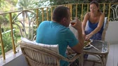 vinho : Woman and man have lunch sitting at the table on the balcony. Man drinking alcohol Vídeos