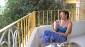 холодный : Woman eats ice cream on the balcony Стоковые видеозаписи