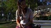 pet friendly : A woman sits on a bench in the park and plays with a kitten on her lap Stock Footage
