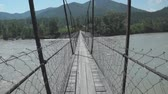 tumultuous : Walking on a suspension bridge across the turbulent river (Katun river in Altai region, Russia) Stock Footage