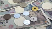 Close up of Japanese coin yen falling on banknotes 1000 and 10000 yen background. Super slow motion 120 fsp with sound. Stok Video