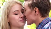 romance : Close up of young couple kissing  in  park  .Shooting with a tripod