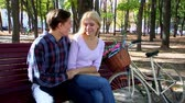 city : Yong couple with white retro bike in autumn park. Romantic date on park bench. Man tenderly holds her hand and said something to her. Happy girl laughs. Nearby is a bike and basket of flowers. Shooting with tripod.