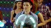 friends : Man with friends keeps disco ball and dancing in nightclub. 4k. Large group people wearing party hat have fun and dance in nightclub. Stock Footage