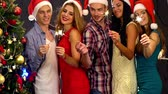 grupo : Friends under Christmas tree. People with sparkler under Xmas tree. Men and women in Santa hat dancing in holiday fun nightclub party. Slow motion.