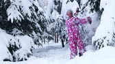 travessura : Energetic child in winter snow outdoor on walk. Girl go in fur tree park alone without parents .