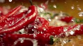 rod : Slow motion of falling chili red pepper pods under running splash spray of water streams on rustic woode table in a country style. Farm organic fresh products.
