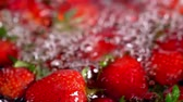 優しい : Strawberry fruit infused water. Close up of crop of picked freshly red berry and green leaves with horizontal motion from right to left. 動画素材