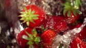 mercadoria : Strawberry with leaves close up under running water streams. Washing fruits before eating in colander. Crop of picked freshly red berry.