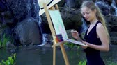 festőállvány : Girl draws on plein air. Young woman with easel and watercolor paints paints flowers on green grass in city park. Mountain waterfall and lake on background.