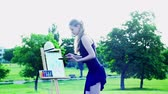 sendas : Girl draws on plein air with light wind. Young woman with easel and watercolor paints painting flowers on green grass and asphalt paths city park. Camera moves around artist wear black evening dress. Archivo de Video