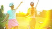 hélio : Children in helmet on bicycle rising sun salute in summer park on hillock with city on horizon . Color tone on shiny sunlight background.