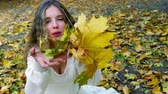 buquê : Autumn girl in fashion in lyrics style. Beautiful woman blowing on bouquet of fall leaves.
