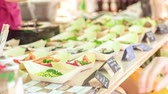 de baixa caloria : A person taking business card from the food stand with prepared raw food dishes Stock Footage