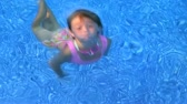 Cute little girl swimming underwater  in clear blue water and coming up smiling.  Stock Footage