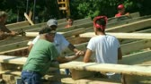 Crew discussing barn planning, with workers building framework in background.