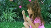 kabarcık : Cute little girl in pink dress sitting is grass blowing bubbles and laughing.