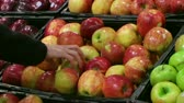 Woman selecting fresh red apples in grocery store produce department.