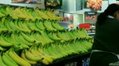 Employee stocking large banana display while working in produce department of supermarket. Stock Footage