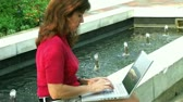 Close-up of female working on laptop while relaxing by fountain in park.