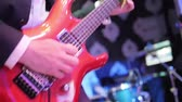 improvise : Playing guitar close up slow motion. Male hand fingers press chords holding notes on fretboard of new red shining electric guitar. Guitarist performs live at concert club. Rock star solo photo flashes Stock Footage