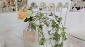 senhor : Green wedding decor on chair for reception close up. Flower bouquet and wild ivy twigs used as decoration at white chair arranged in guest seat area. Wedding plan florist work floral elements decision