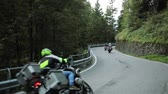 motorcyclists : Motorcycle riders ride bikes mountain wood road up one by one slowly. Group of unrecognizable men motorcyclists on motorbikes in helmets protection suits drive twisting serpentine road lane with rails Stock Footage