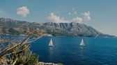 レガッタ : A sailboats the Adriatic sea mountains background island Sv. Nikola 動画素材