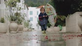 legrační : A little boy in rubber boots walks through puddles with an umbrella during the rain Dostupné videozáznamy