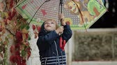derramar : Sad little boy stands under an umbrella during the rain on a background of autumn yellow leaves