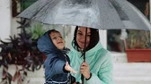 legrační : Young mother with her son hide under an umbrella during the rain Dostupné videozáznamy