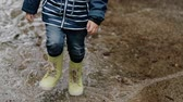 legrační : Little boy walks through puddles in rubber boots during the rain