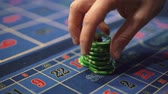 şans : Dealer works in the casino moving chips with his hands at the gaming table