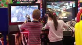 play video game : Kids playing shooter video game in game center
