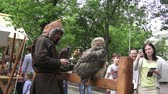 berkut : Times and Epochs festival on Moscow streets. Man holding in hand hunting predatory bird falcon hawks used for sporting and hunting for the beast