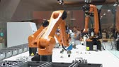 almanca : Automation solutions of the future with robot arms on Kuka stand on Messe fair in Hannover, Germany Stok Video