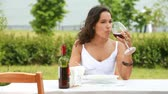 local : Beautiful young woman enjoying her meal and local red wine in the open air