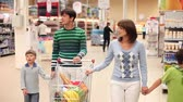 empurrando : A family of four rolling a trolley with products along the supermarket, looking around and talking Stock Footage