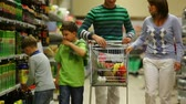 corredor : A family of four walking along the beverage row in the supermarket, the sons putting drinks into the trolley Vídeos
