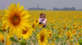 słonecznik : A young woman walking among sunflowers with her little son in hands