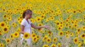 цветение : A young woman walking among sunflowers and brushing them