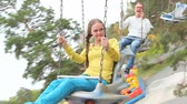 passeio : Two teenagers having a good time on a carousel in the park Stock Footage