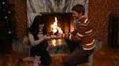 lareira : A young a man proposing to his valentine sitting at a fireplace