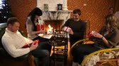 lareira : Four young people sitting at a fireplace and unpacking Christmas presents