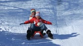 сугроб : Happy parents and their children riding on sledges in winter