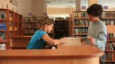university : A boy returning books in library and a girl taking them Stock Footage