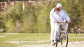 Two senior people riding a bike